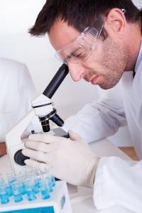 Patolog som ser i mikroskop