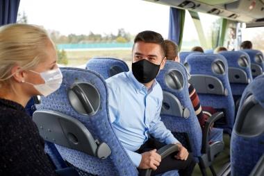 to unge busspassasjerer med munnbind